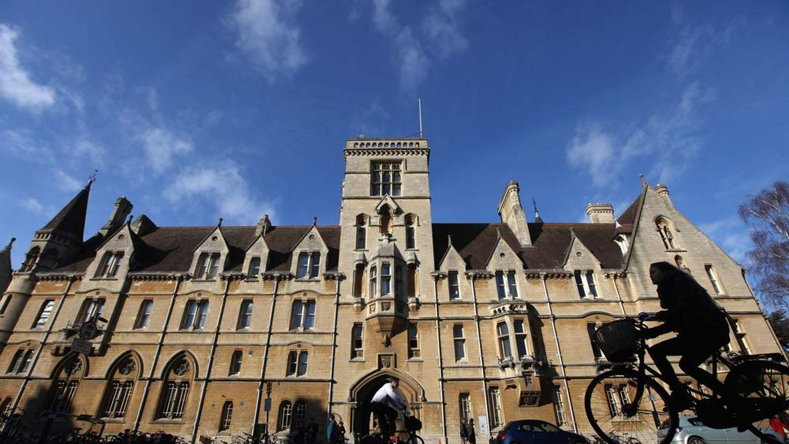 A woman cycles past Balliol College in Oxford city centre.