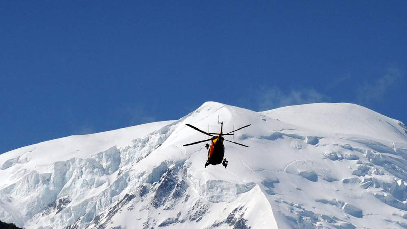 A rescue crew of the emergency services flies over the Mont Blanc massif in an helicopter on July 12, 2012 in Chamonix, in the French Alps, to the Mont Maudit, a mountain in the Mont Blanc Massif where an avalanche killed at least six people