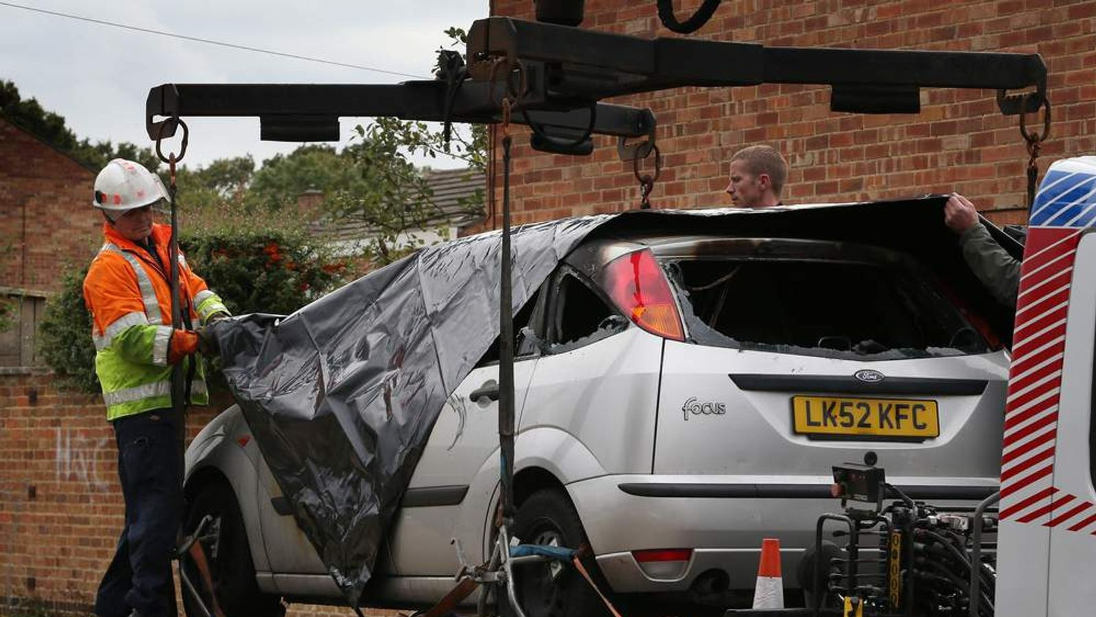 Police remove a burnt out car near a house where five people died in a fire on October 15, 2012 in Harlow, England.