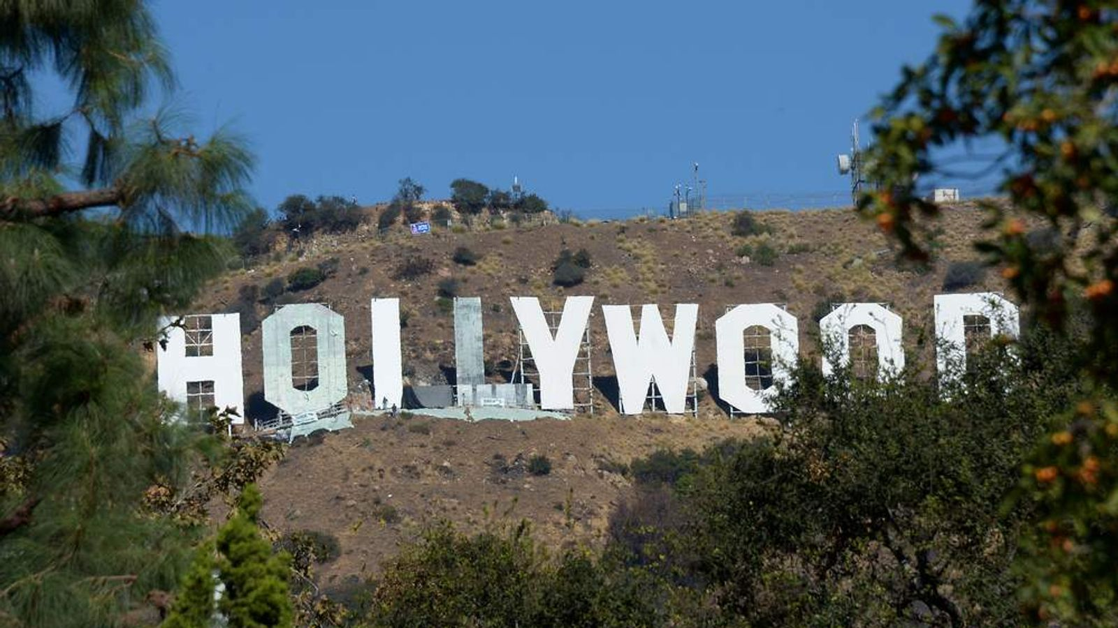 Workers  use window-cleaner style platforms as they strip down the 50-foot (15-meter) tall letters, power washing the corrugated iron and apply nearly 400 gallons of fresh paint while restoring the Hollywood sign on October 26,2012.