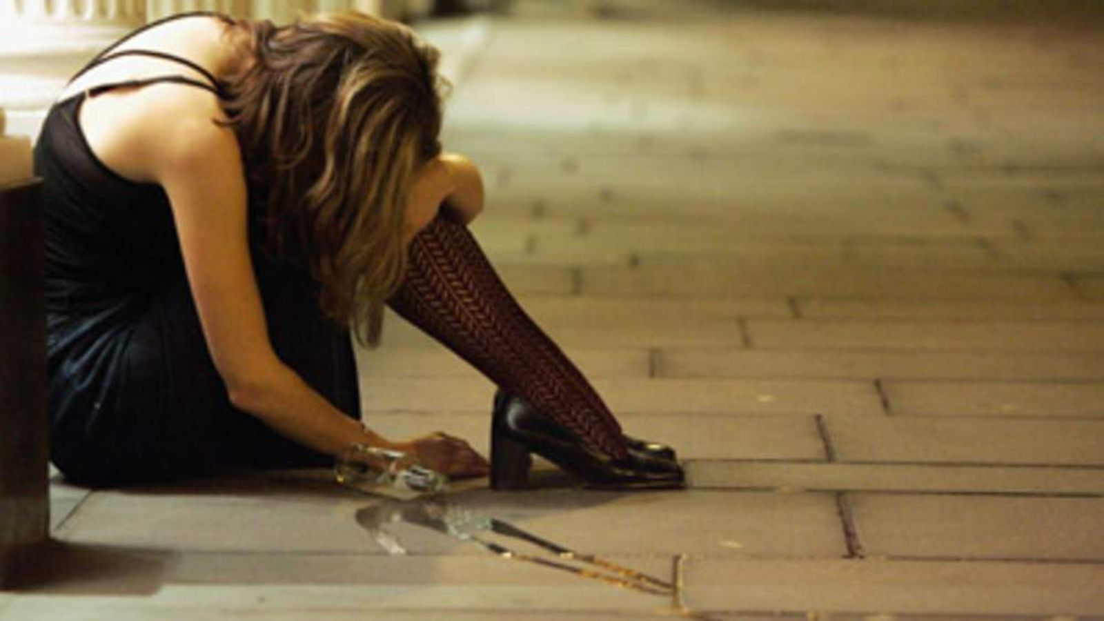 A woman drinker slumps on the pavement in Bristol