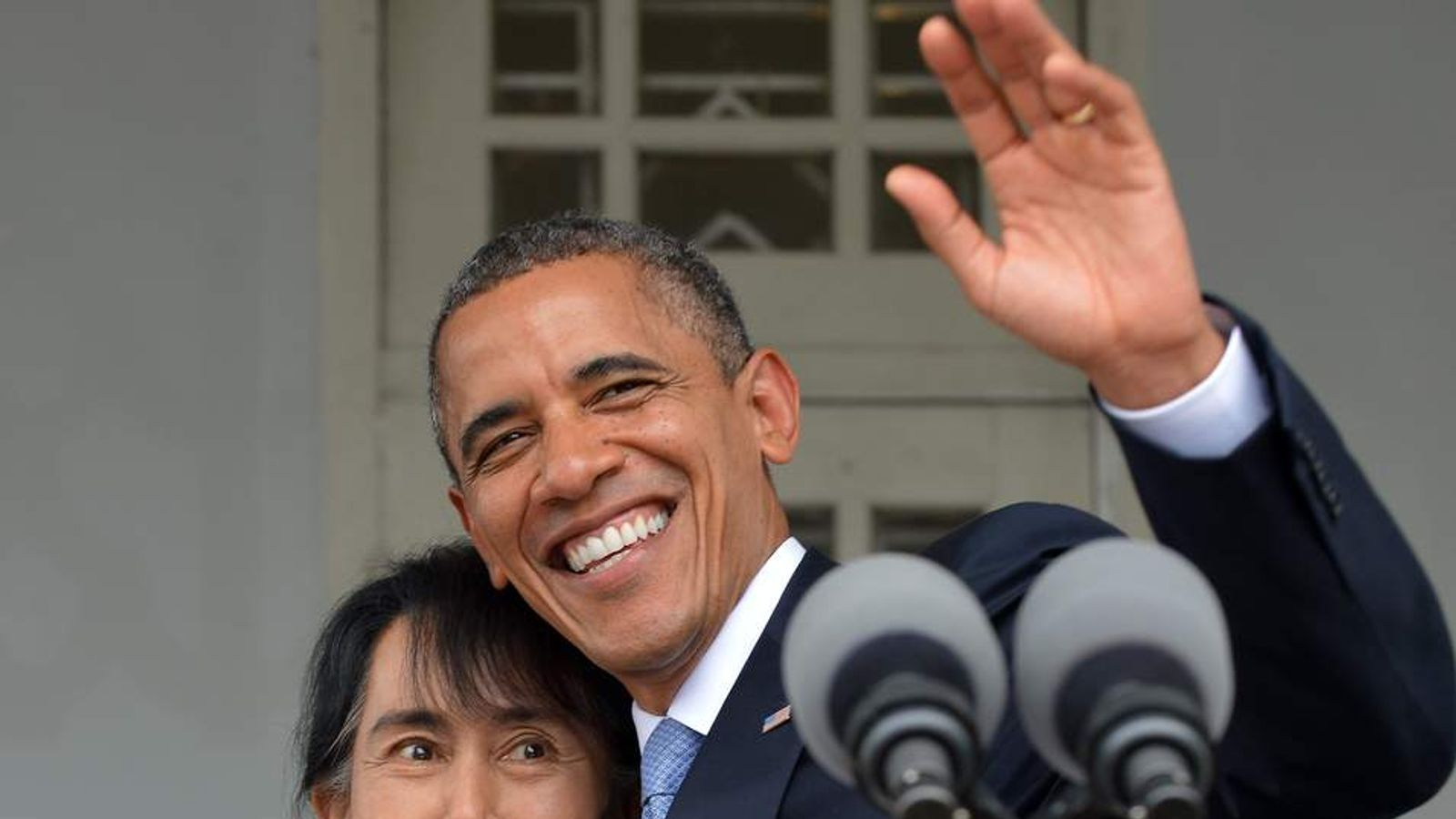 Obama (R) waves holding Myanmar opposition leader Aung San Suu Kyi after making a speech at her residence