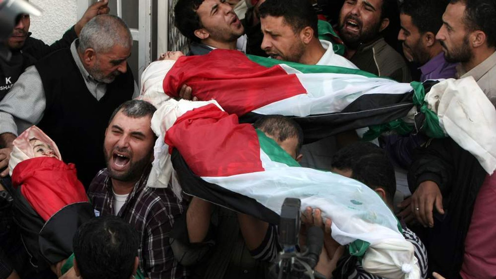 Palestinian mourners carry the bodies of children from the al-Dallu family after Israeli air strike