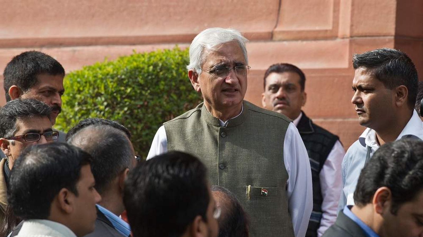 Indian Foreign Minister Salman Khurshid (C) interacts with the media at Parliament house during the winter session in New Delhi
