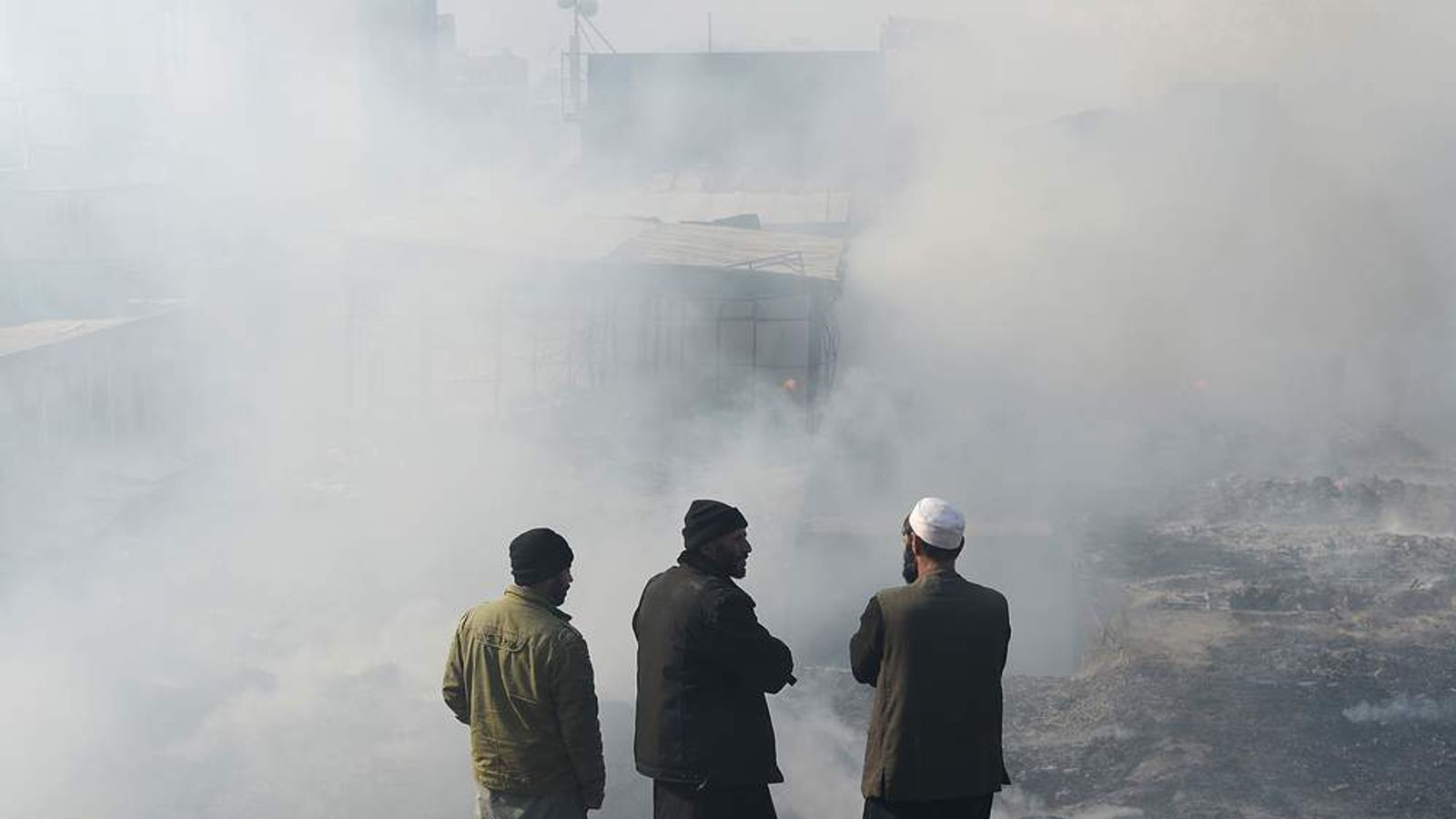 Afghan shopkeepers look on as they stand over the smoldering remains of shops