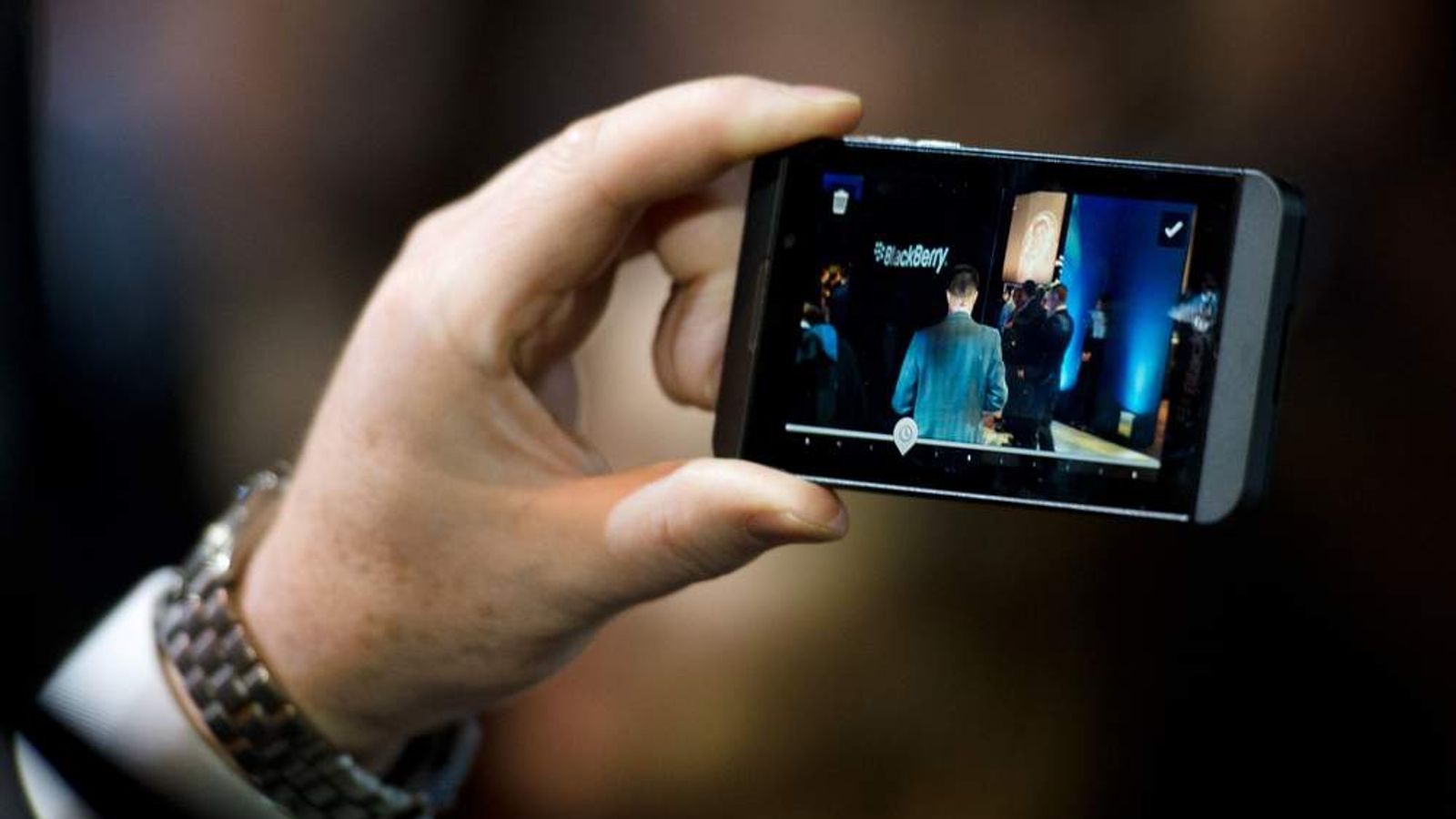 A member of the RIM team poses with one of the new touchscreen Z10 Blackberry devices