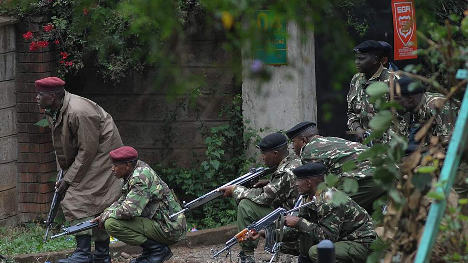 Armed Kenyan policemen take cover outside the Westgate mall in Nairobi, Kenya