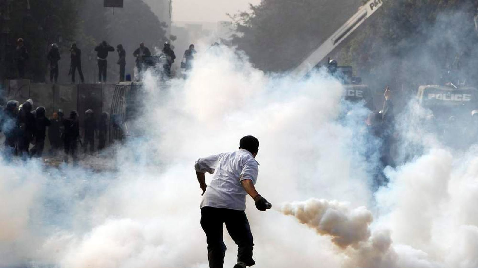 A protester returns a tear gas canister to the riot police in Cairo