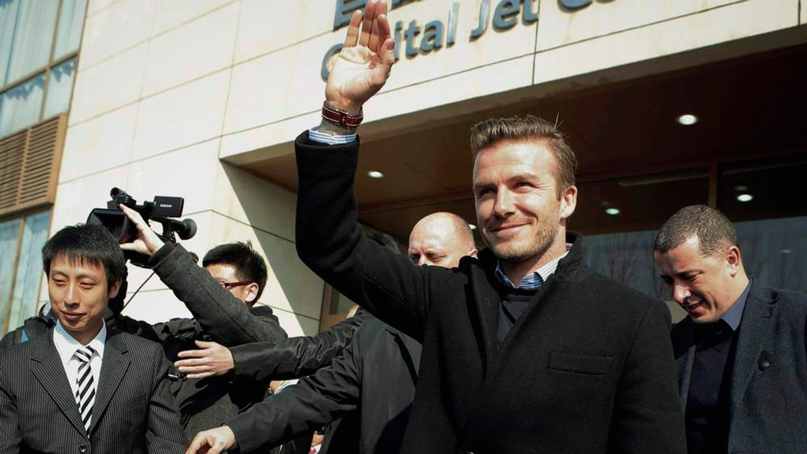 Former England captain Beckham waves after he arrives at an airport in Beijing