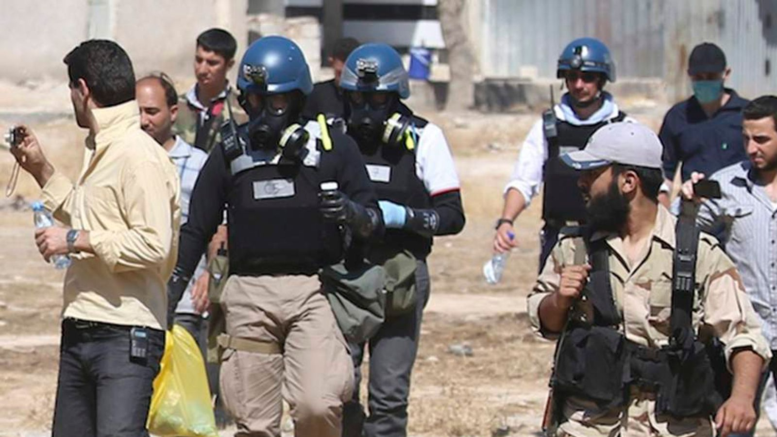 U.N. chemical weapons experts wearing gas masks carry samples collected from one of the sites of an alleged chemical weapons attack while escorted by Free Syrian Army fighters in the Ain Tarma neighbourhood of Damascus