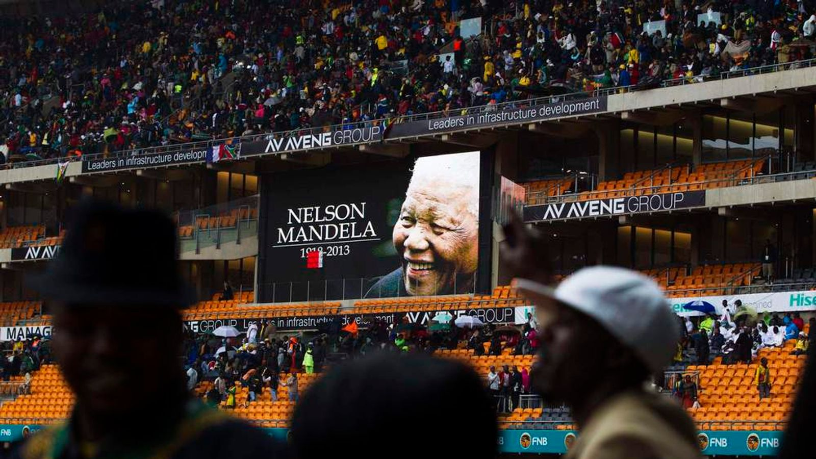 Pepole sing and dance at a mass memorial for Mandela in Johannesburg