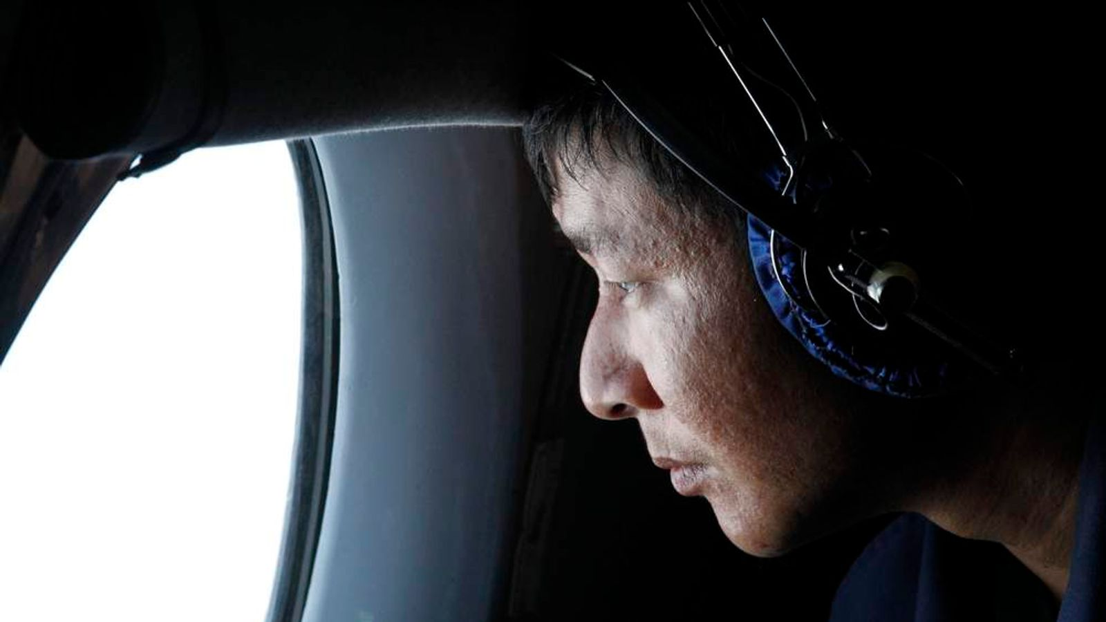 A military officer looks out a window during a search and rescue mission onboard an aircraft belonging to the Vietnamese airforce off Vietnam's Tho Chu island