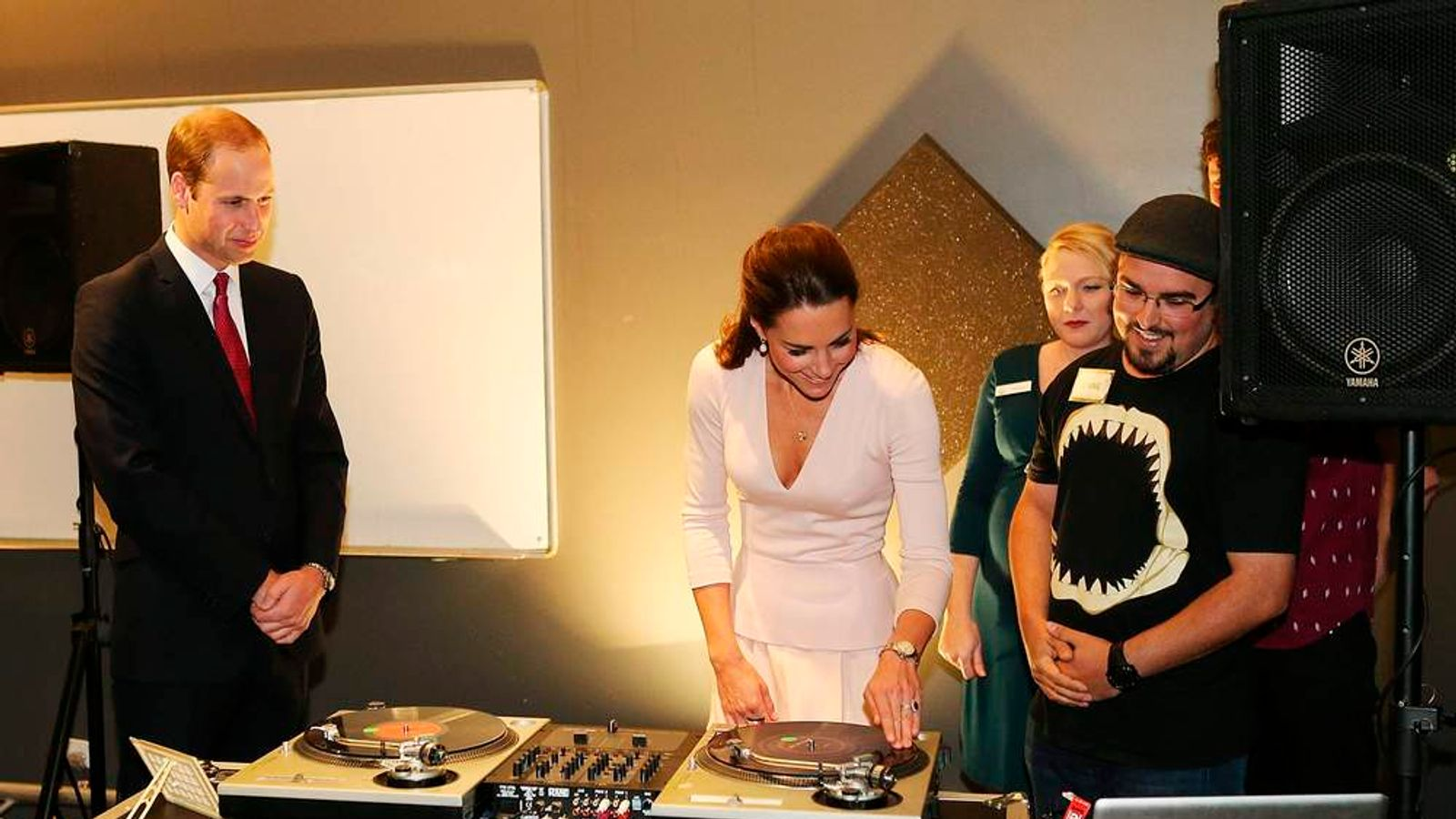 Prince William, Duke of Cambridge, looks on as Catherine, Duchess of Cambridge is shown how to play on DJ decks at the youth community centre, The Northern Sound System in Elizabeth near Adelaide