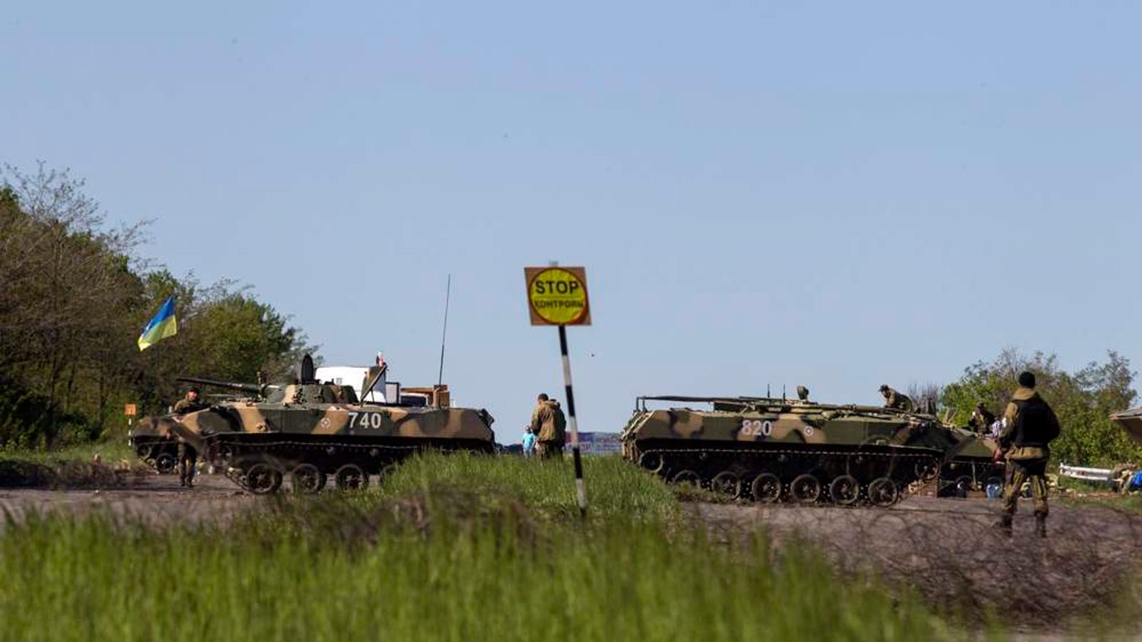 Ukrainian soldiers walk near armoured personnel carriers at a checkpoint in near the town of Slaviansk, in eastern Ukraine