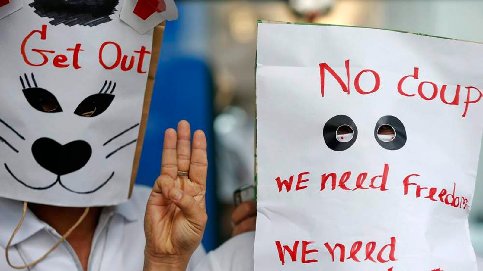 Anti-coup protesters wear paper bags with messages written on them and flash a three finger sign during a protest at a shopping mall in Bangkok