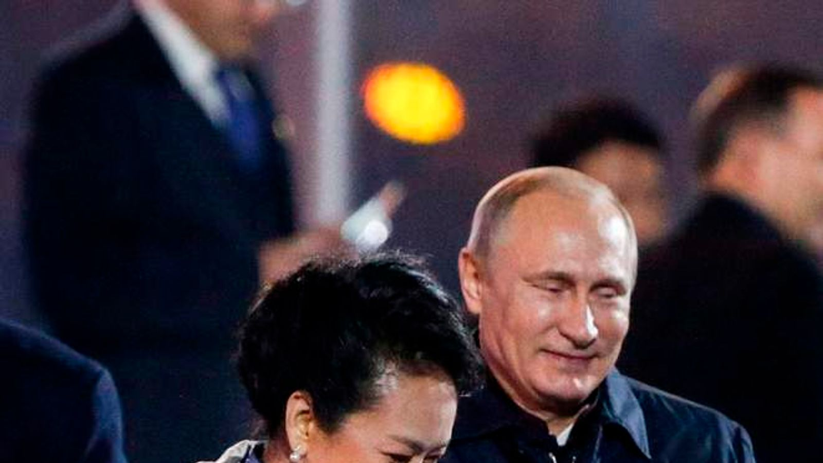 Russia's President Putin helps put a blanket on Peng, wife of China's President Xi, in Beijing