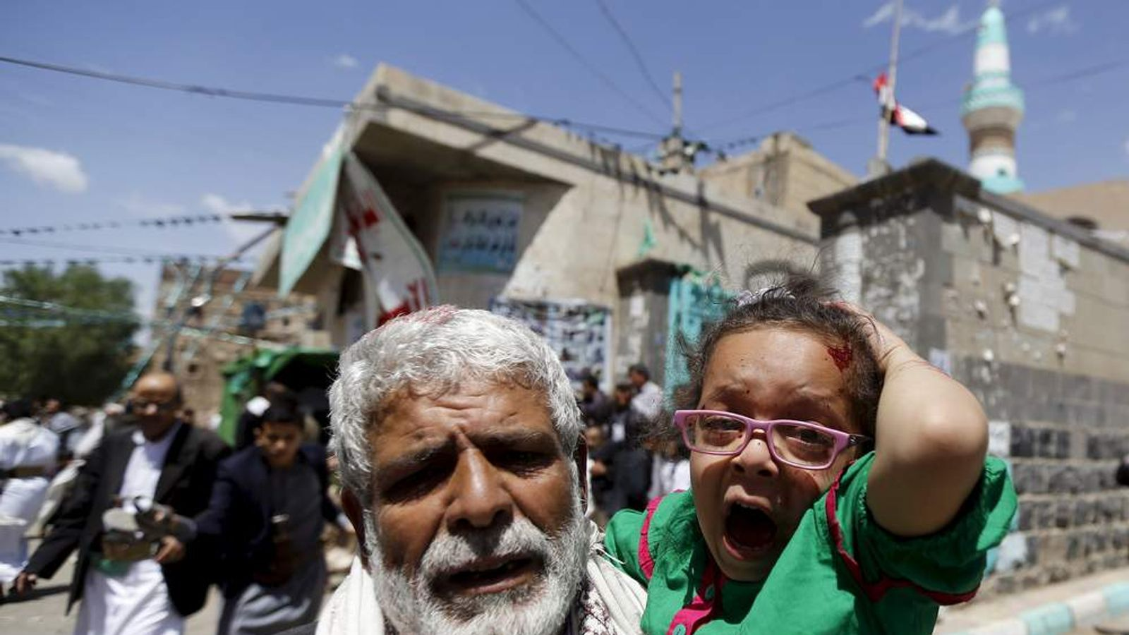 An injured girl reacts as she is carried by a man out of a mosque which was attacked by a suicide bomber in Sanaa