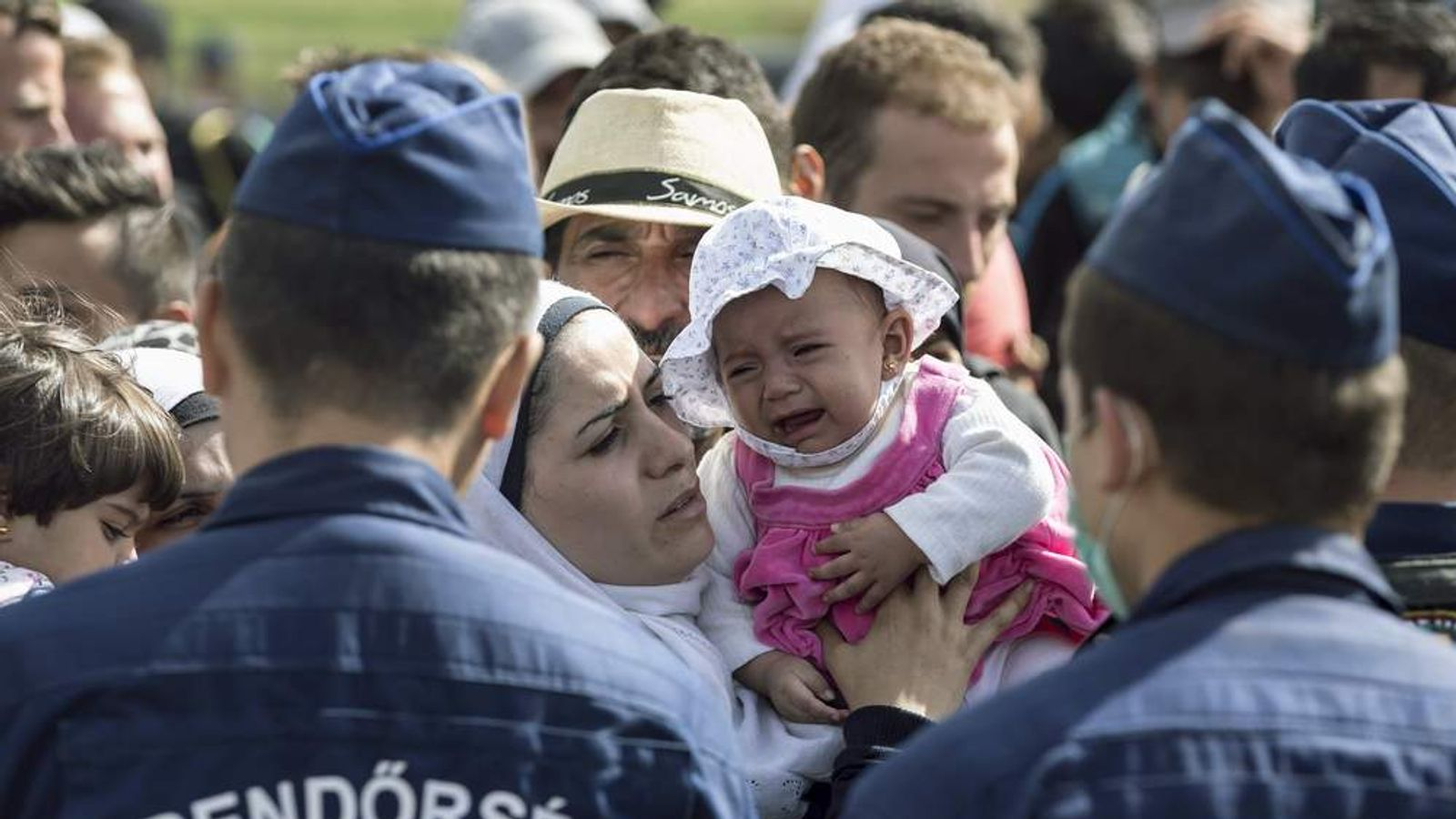 A migrant kisses a child who is crying as they stand in front of Hungarian police officers while waiting to board buses at a collection point in the village of Roszke, Hungary