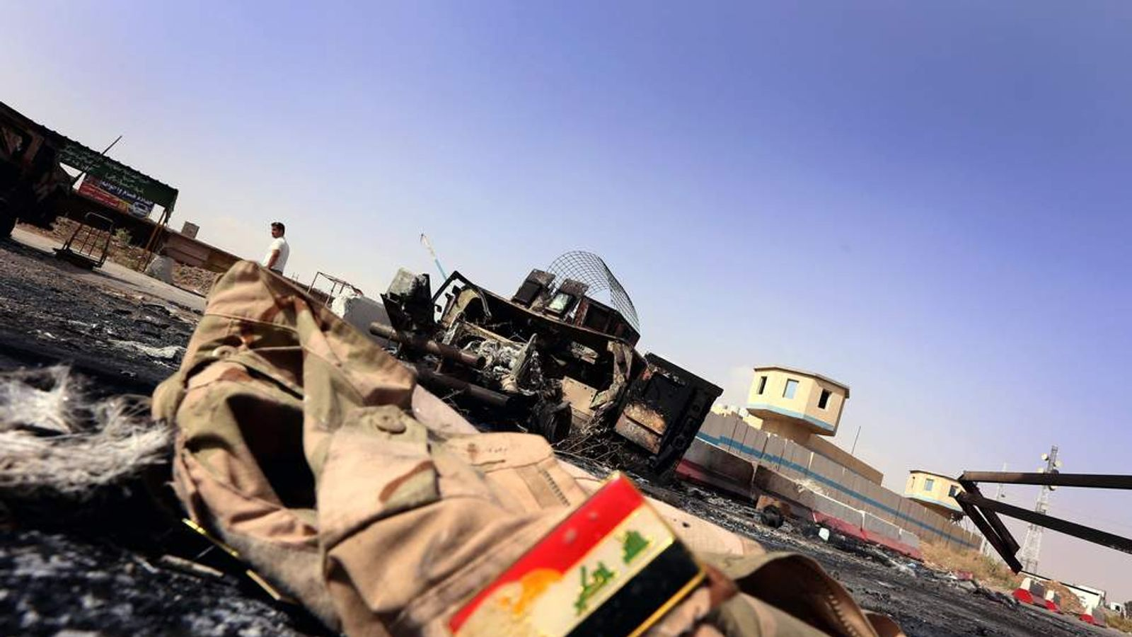 The jacket belonging to an Iraqi Army uniform lies on the ground in front of the remains of a burnt out Iraqi army vehicle.