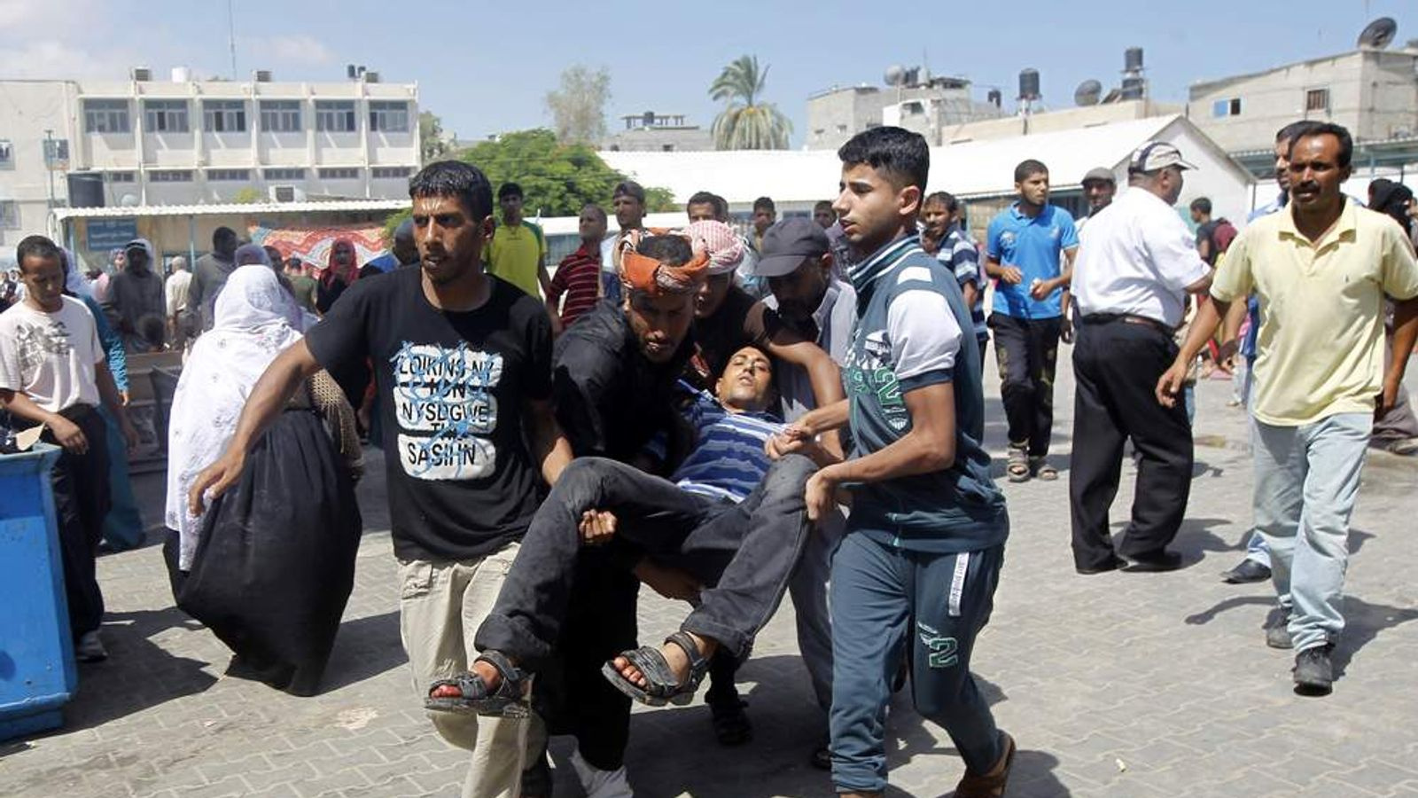 Palestinians carry an injured man following an Israeli military strike on a UN school.