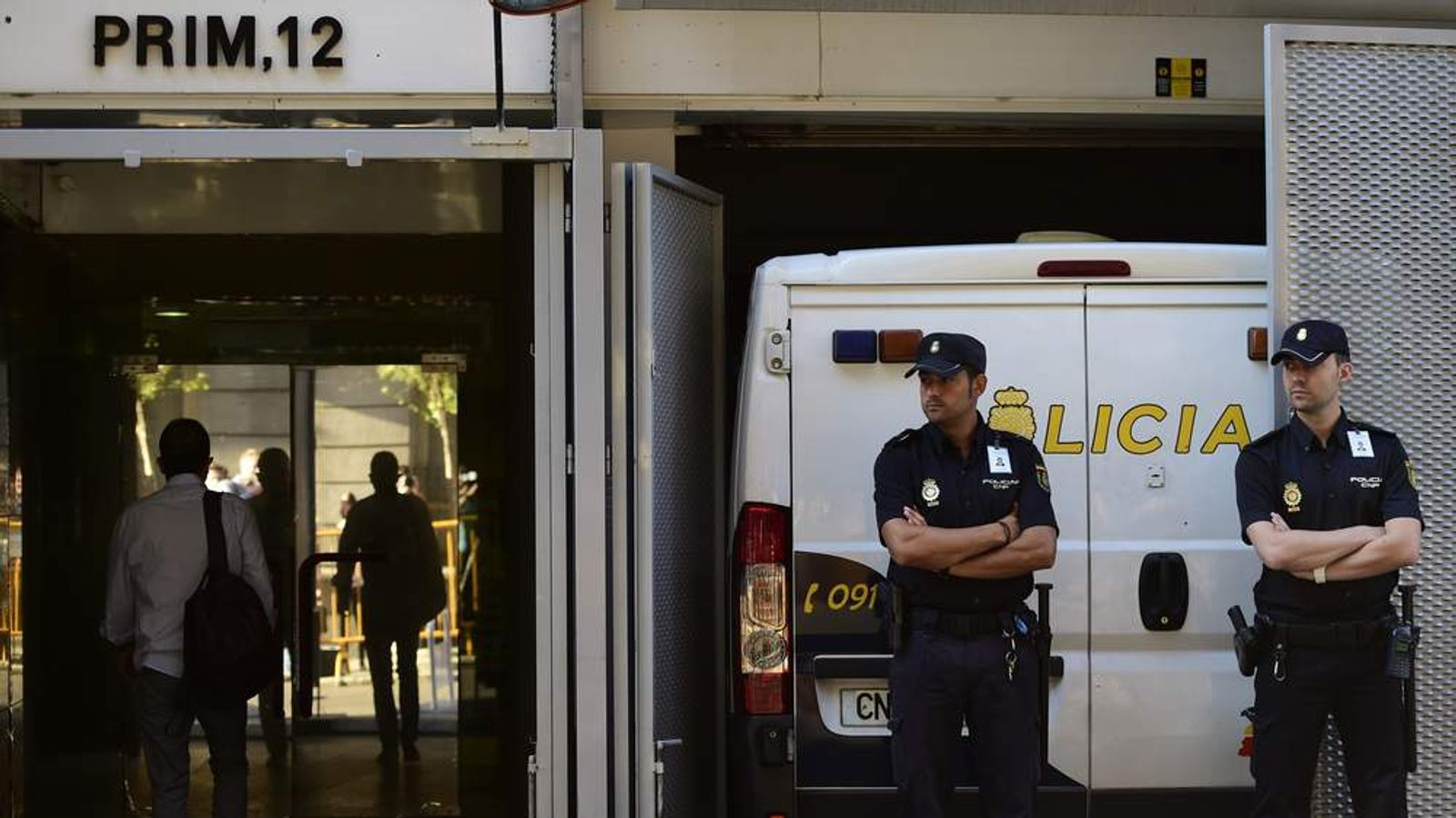 Spanish policemen stand guard as a police van carrying the parents of  Ashya King