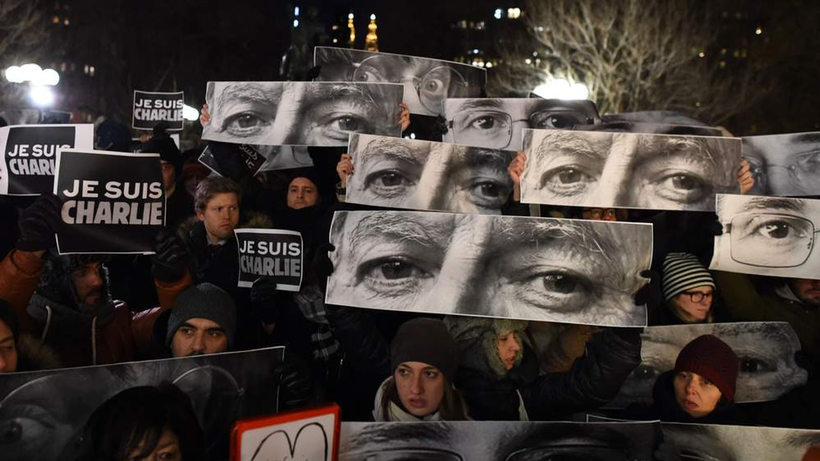 People hold signs with words reading 'Je Suis Charlie' (I Am Charlie) beneath an electronic display echoing the sentiment outside the Newseum in Washington DC