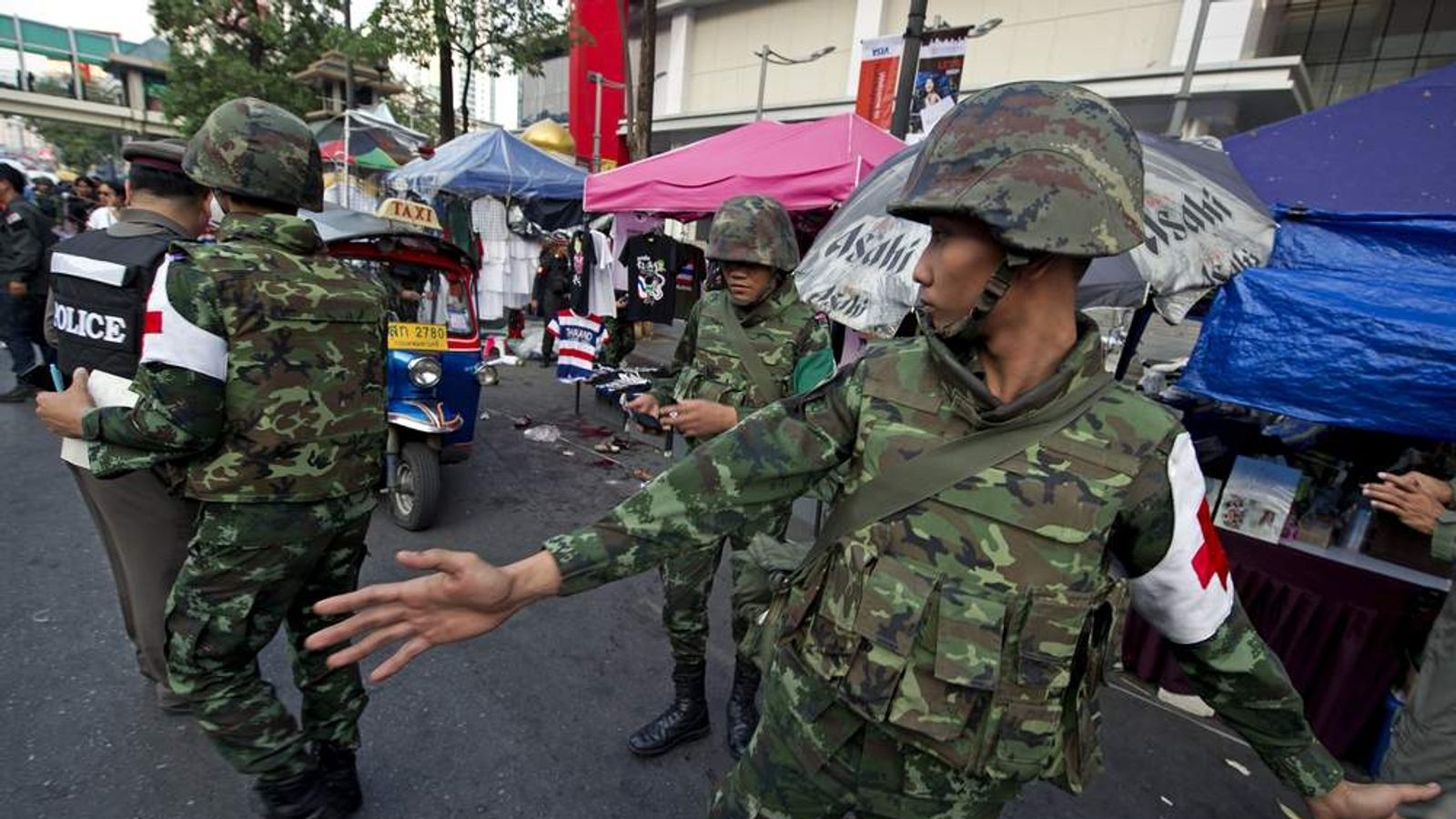 Thai soldiers inspect the site of bomb blast near an anti-government rally in Bangkok