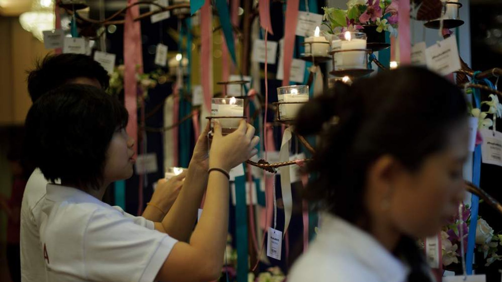 The families of passengers missing on flight MH370 place candles for a prayer vigil in Kuala Lumpur.