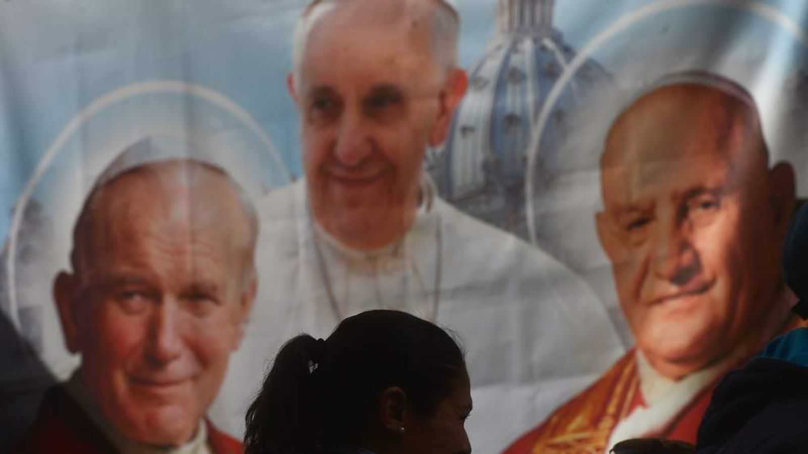 A poster shows the late Popes John XXIII and John Paul II ahead of their canonisation.