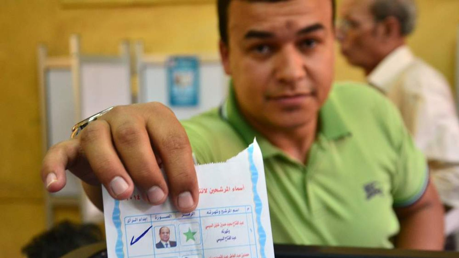 An Egyptian man displays his election card at a polling station