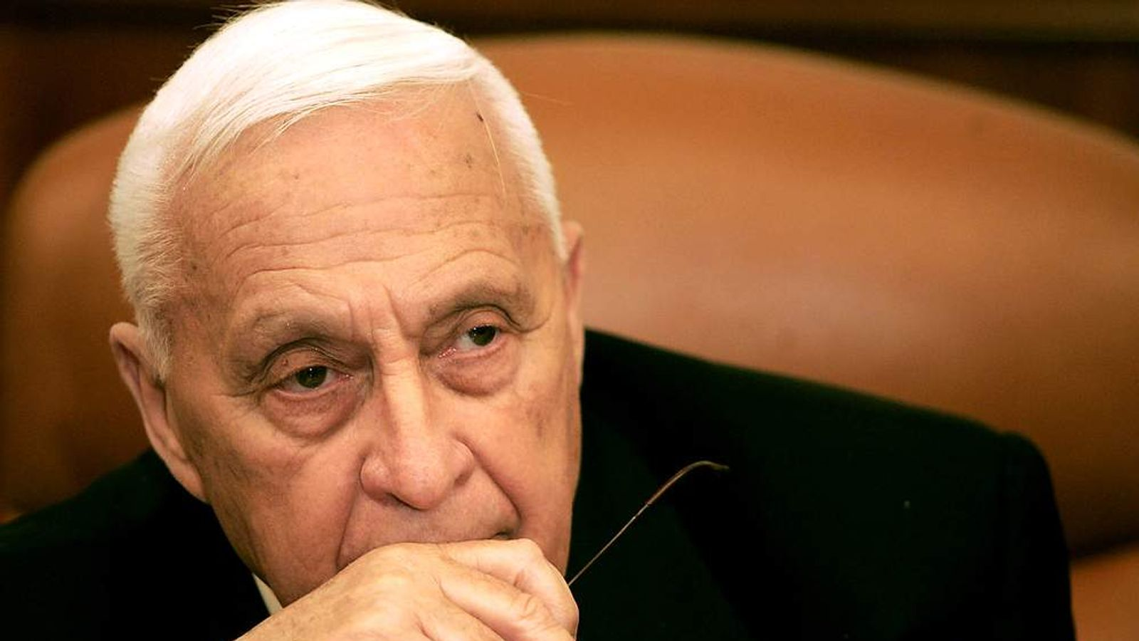 Israeli Prime Minister Ariel Sharon looks on during a ceremony completing the sale of Bank Leumi to a private U.S. investment group