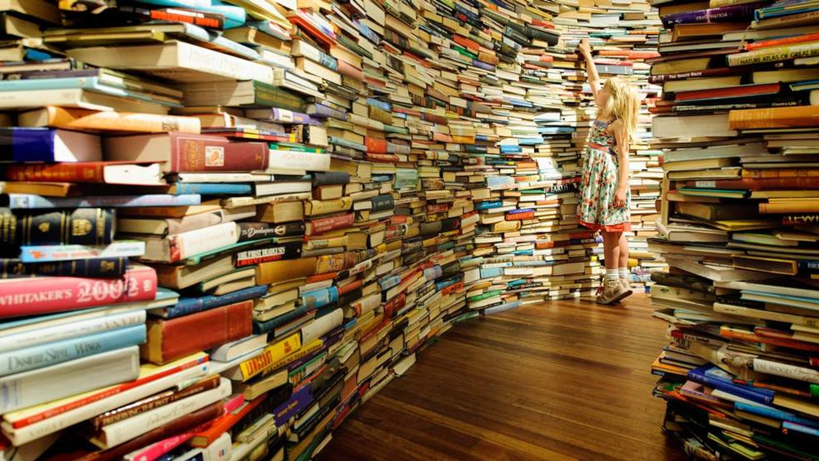 Leona Ryan, from Norfolk, explores the 'aMAZEme' installation, a maze constructed of 250,000 books by Brazilian artists Marcos Saboya and Gualter Pupo, at the Royal Festival Hall, on the southbank, in central London.