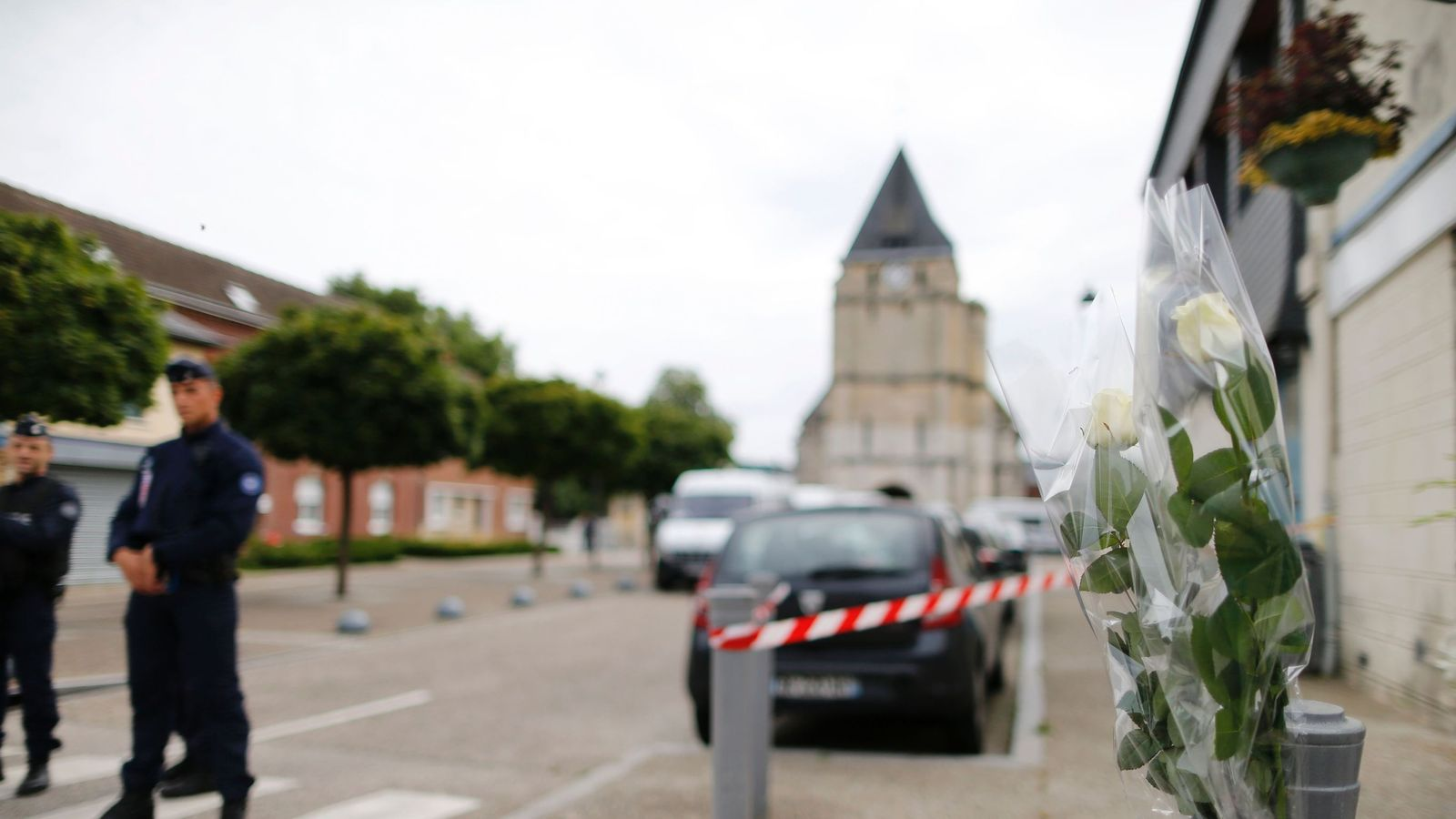 Flowers laid in tribute to Father Jacques Hamel as police officers stand guard the street to the Saint-Etienne church.
