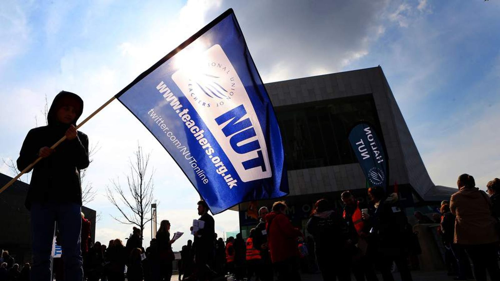A young boy in Liverpool's Mann Island holds aloft a flag in support for the Nation Union of Teachers (NUT) during a one-day walkout