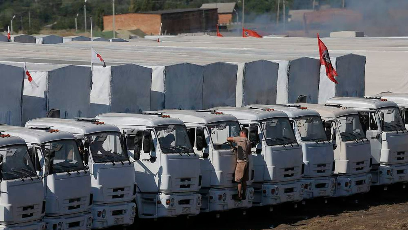 A Russian convoy of trucks carrying humanitarian aid for Ukraine is parked at a camp near Kamensk-Shakhtinsky