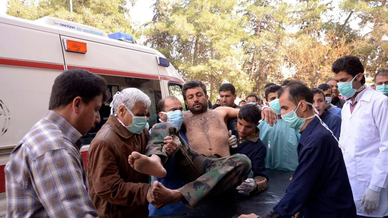 Residents and medics transport a Syrian Army soldier, wounded in what they said was a chemical weapon attack near Aleppo, to a hospital