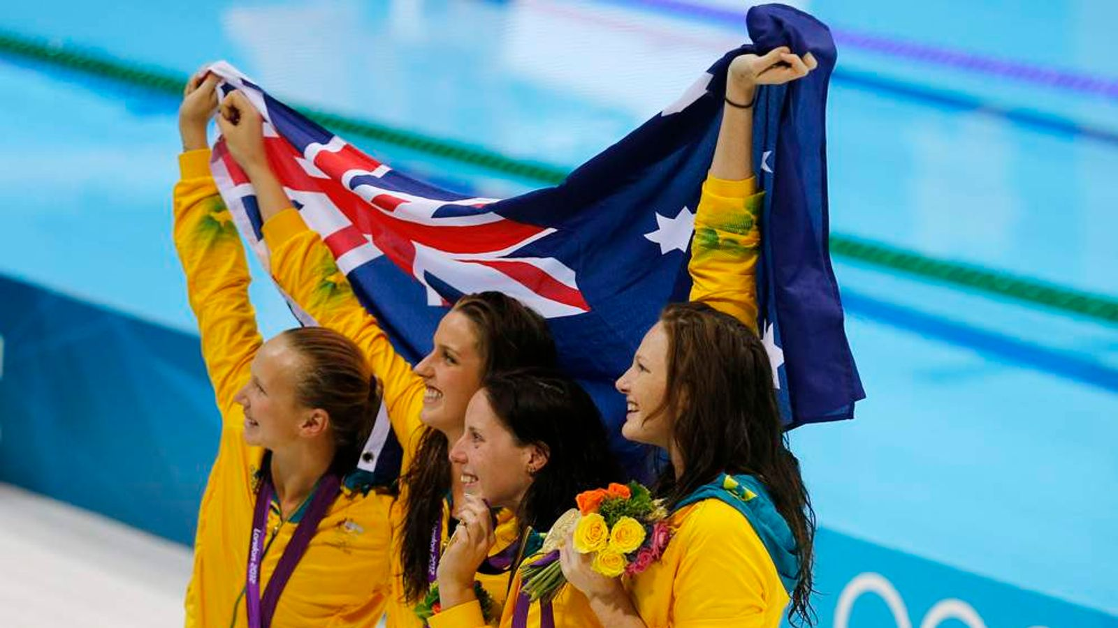 Gold medallists from Australia's team celebrate on the podium during the women's 4x100m freestyle relay victory ceremony at the London 2012 Olympic Games