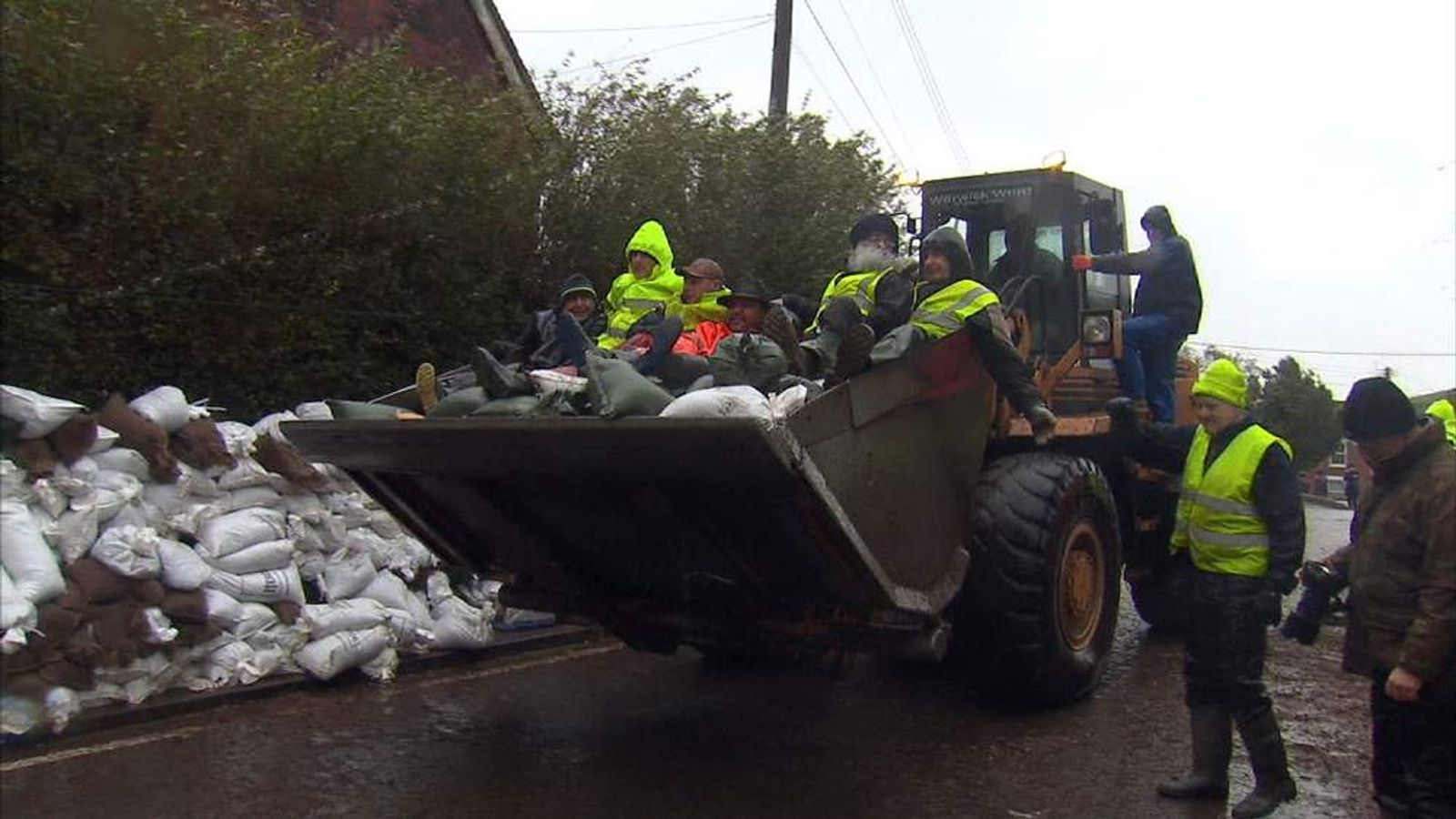 Volunteers and sandbags transported by JCB through floods