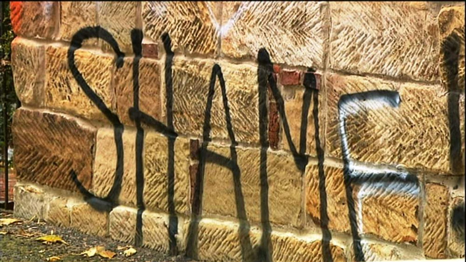 "The word ""shame"" sprayed on the wall"