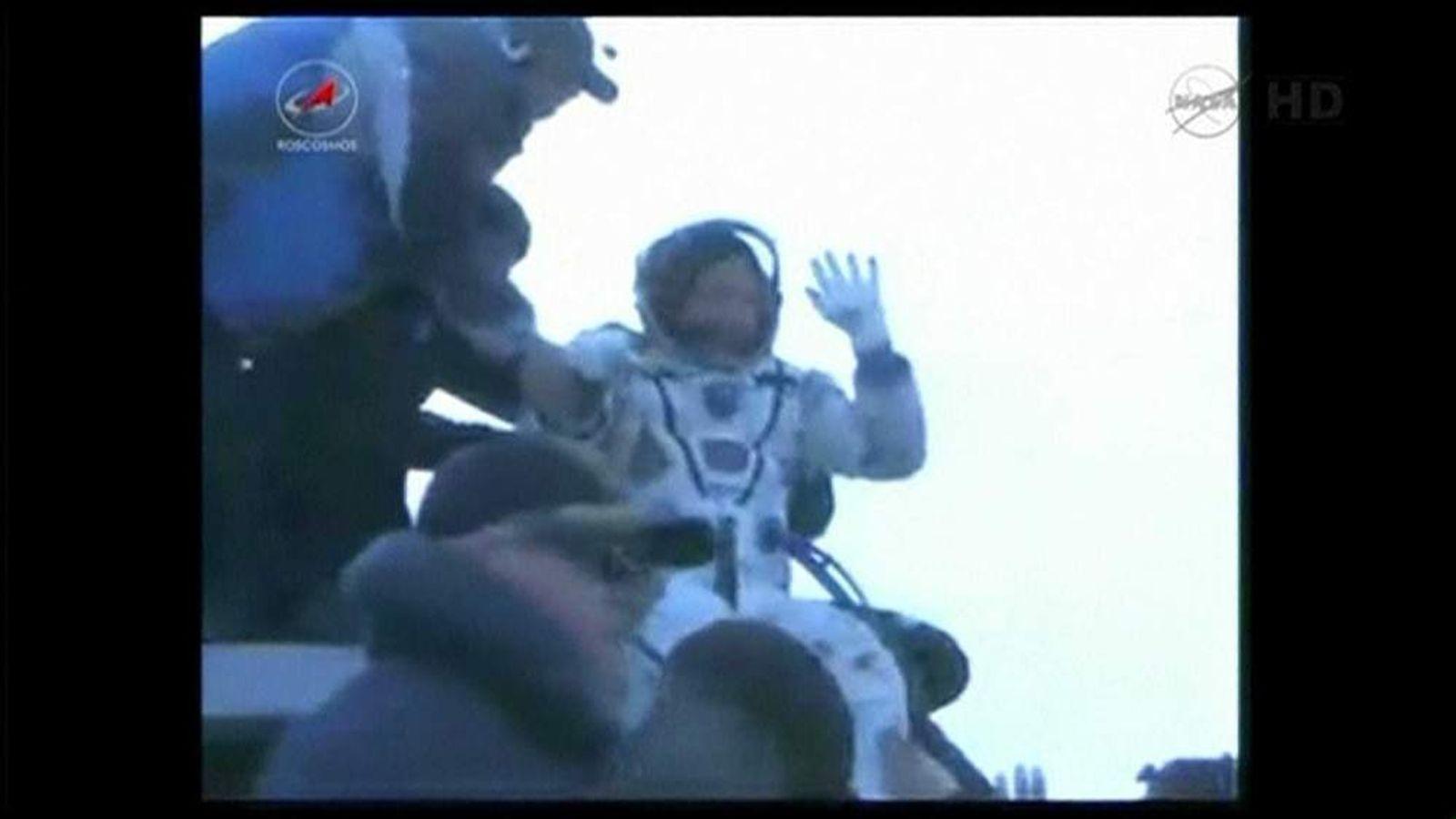 Russian cosmonaut Oleg Novitskiy waves as he is helped out of the Soyuz capsule