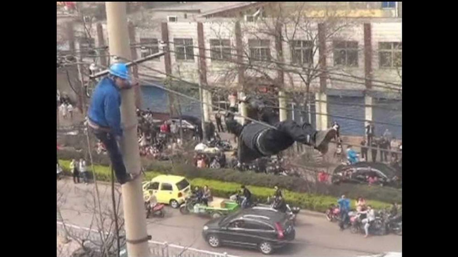 drunk man clings to electricity telephone cables