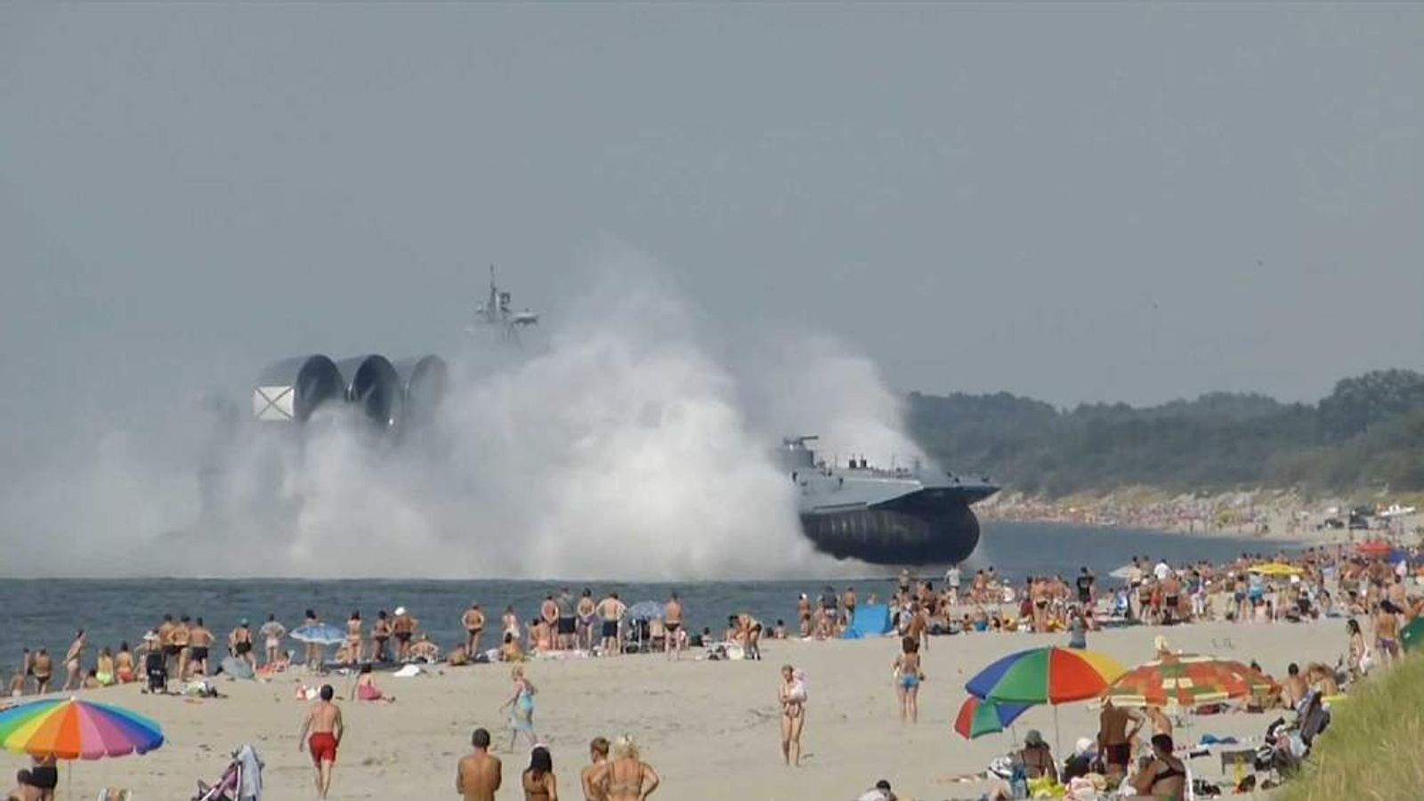 A Russian hovercraft lands on a busy beach