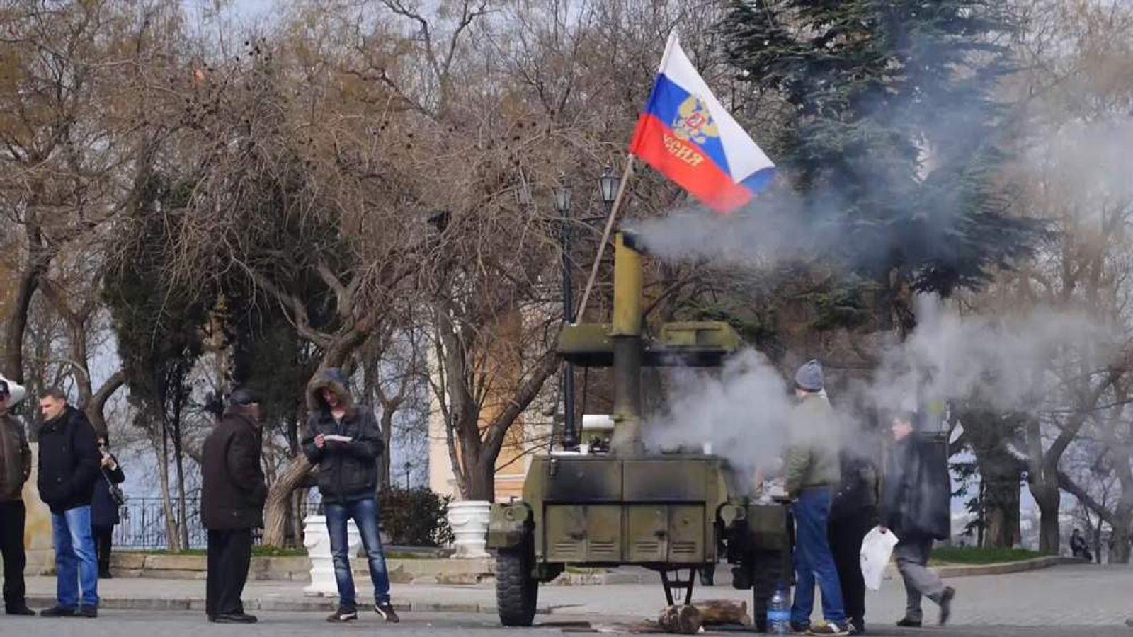 Protesters raise a Russian flag in Crimea, Ukraine