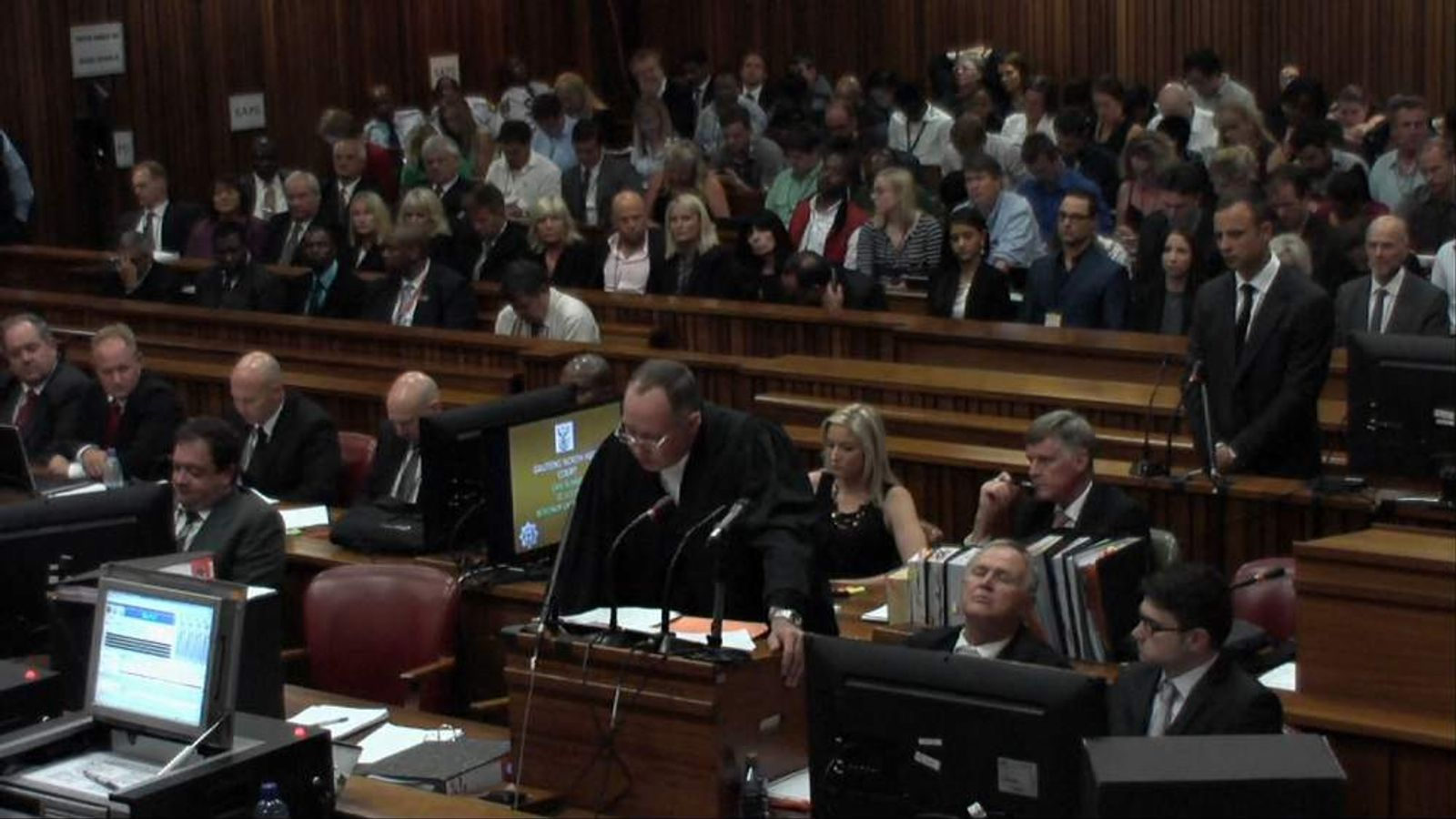 Oscar Pistorius standing behind is defence counsel