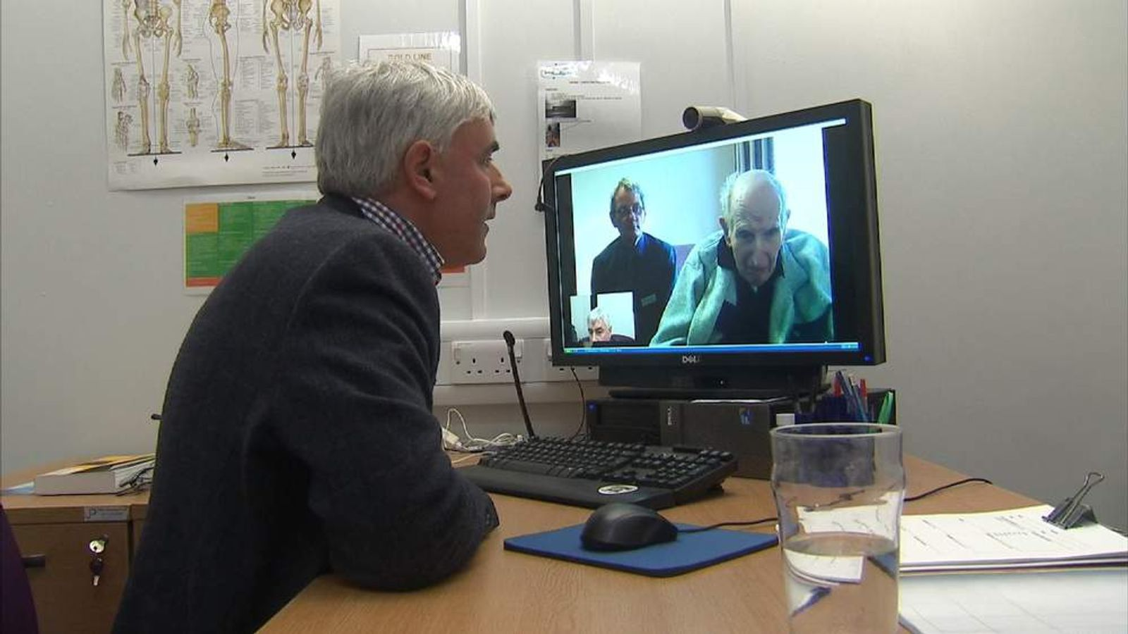 Dr Colin Renwick speaks to a patient in a care home via a webcam
