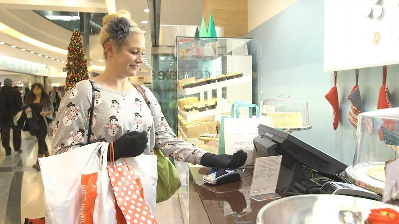 A woman pays for items in a shop using Barclaycard's payment glove at Christmas time