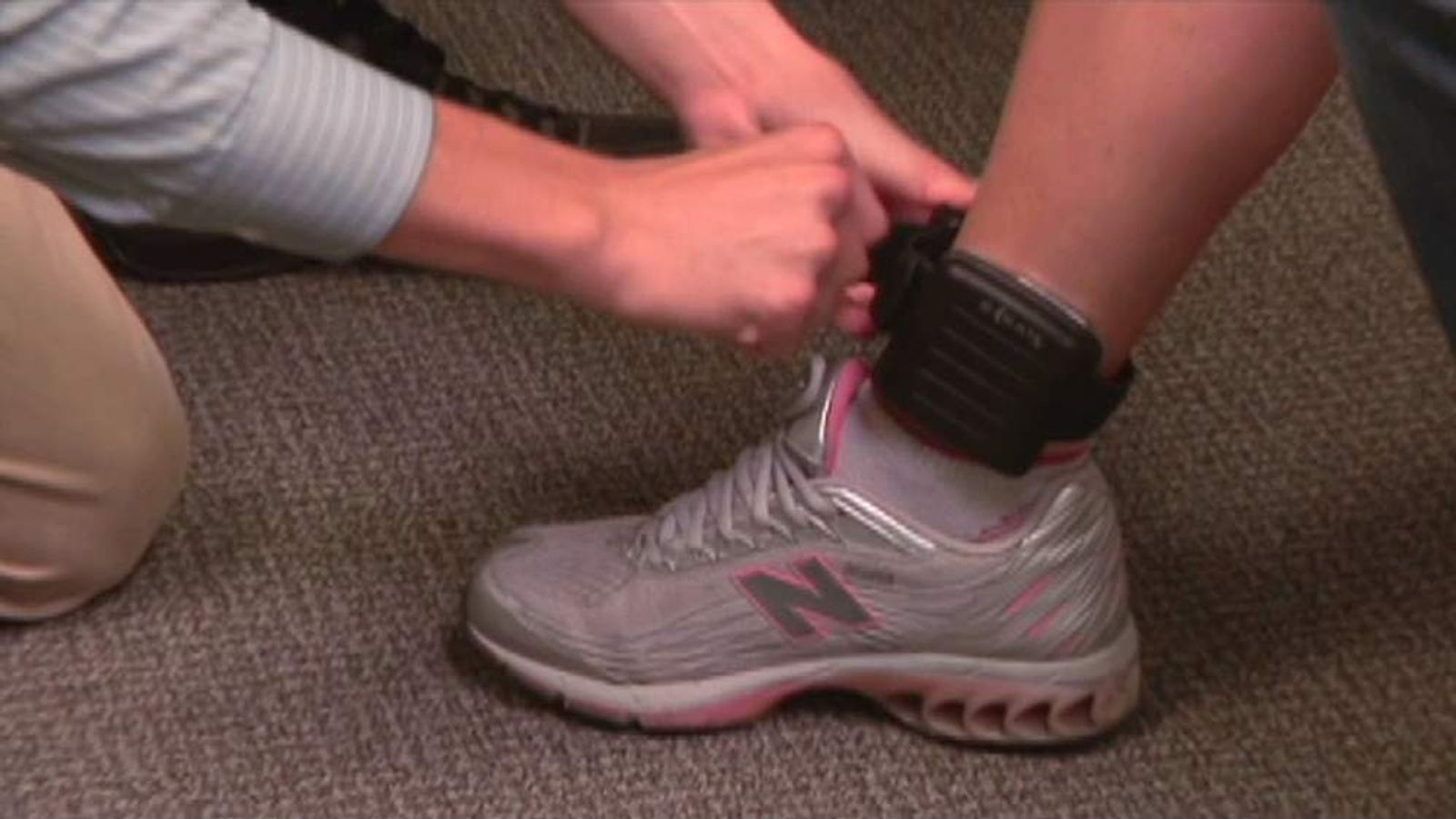 A close up of a Sobriety Tag being applied to an ankle