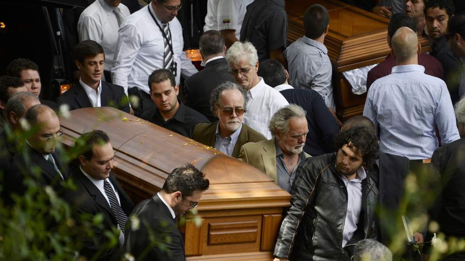 Relatives and friends carry the coffins with the remains of Venezuelan model Monica Spear and her British-born partner Thomas Henry Berry