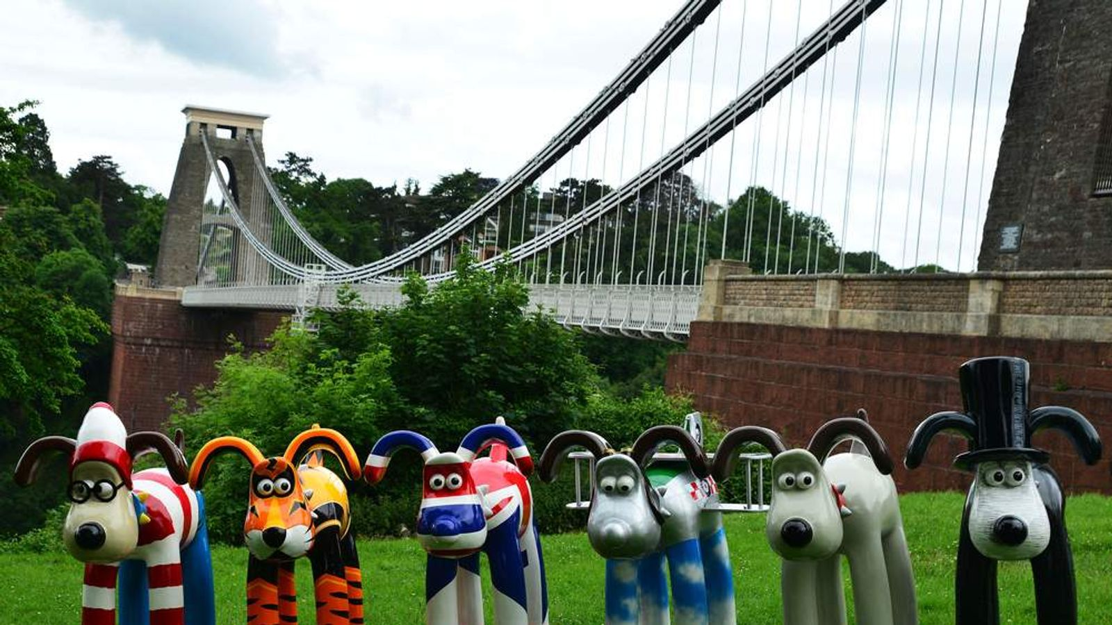 9 painted Gromit sculptures line up at Clifton Suspension Bridge.