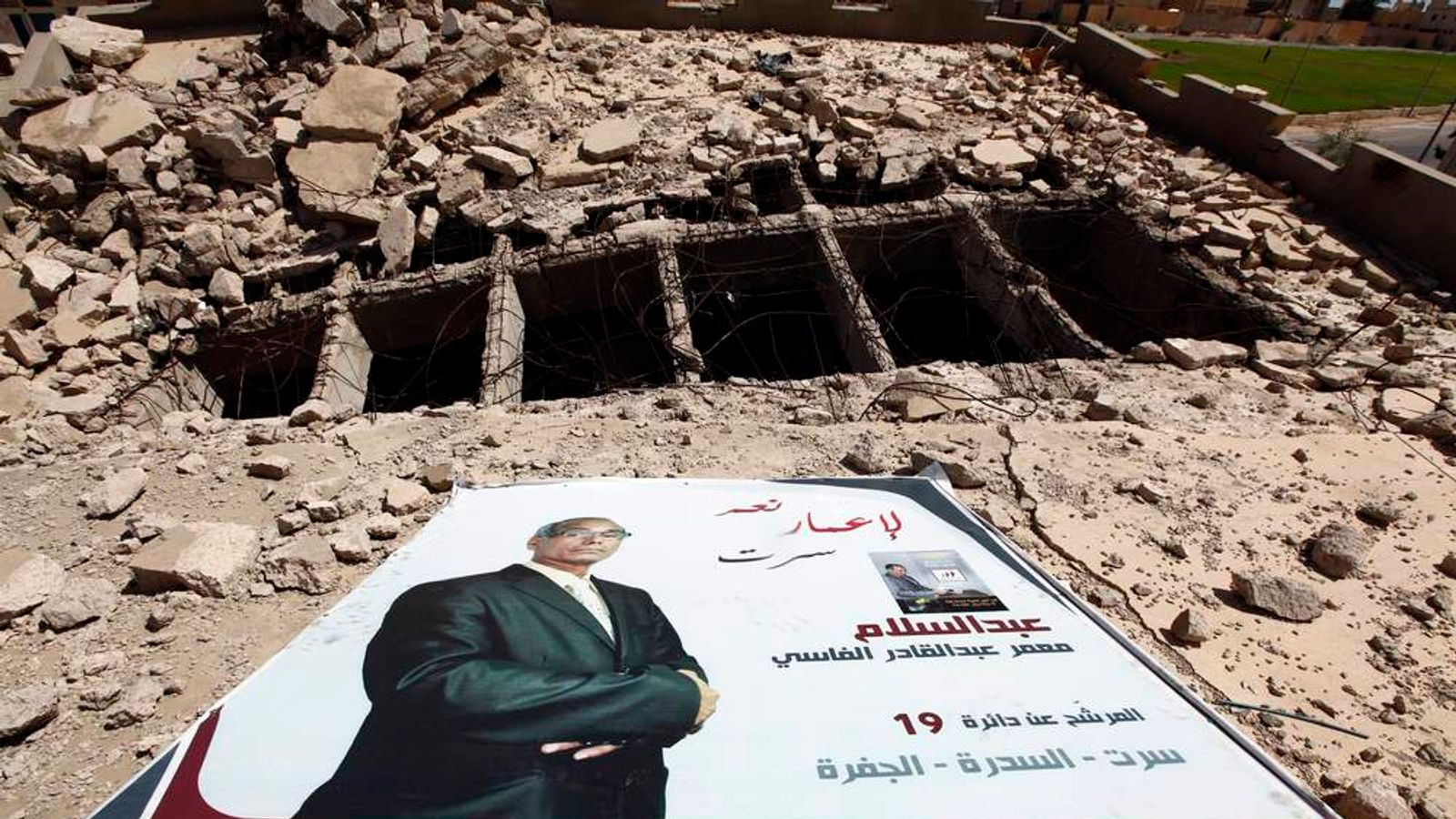 An election poster of candidate Abdulsalam Al Fasi lies on the top of a destroyed building in Sirte, on July 6.